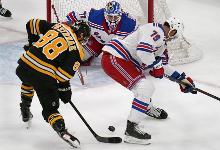 New York Rangers goaltender Keith Kinkaid, center, eyes the puck on a shot by Boston Bruins right wing David Pastrnak (88) during the first period of an NHL hockey game, Saturday, May 8, 2021, in Boston. At right is New York Rangers defenseman K'Andre Miller. (AP Photo/Charles Krupa)