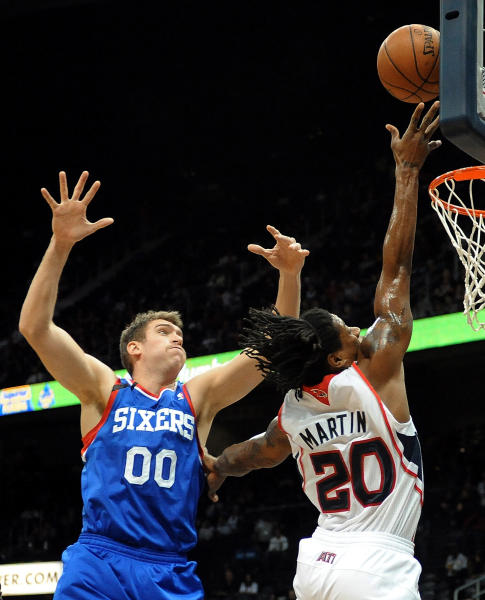 Atlanta Hawks' Cartier Martin (20) goes to the basket in front of Philadelphia 76ers' Spencer Hawes in the first half of an NBA basketball game Friday, Nov. 15, 2013, in Atlanta. (AP Photo/David Tulis)