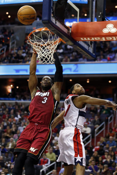Miami Heat guard Dwyane Wade (3) misses a dunk in front of Washington Wizards guard Garrett Temple (17) in the first half of an NBA basketball game on Wednesday, Jan. 15, 2014, in Washington. (AP Photo/Alex Brandon)