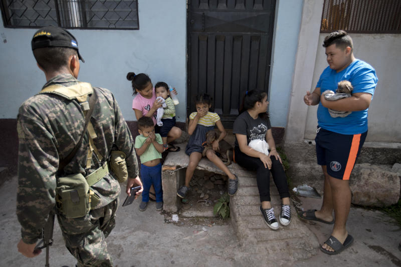 In this photo taken on Aug. 22, 2019, a Honduran soldier watches children while a house is being sprayed in an attempt to control the spread of mosquito-borne diseases in Tegucigalpa, Honduras. At least 135 people have died from dengue this year in Honduras, nearly two-thirds of them children. (AP Photo/Eduardo Verdugo)