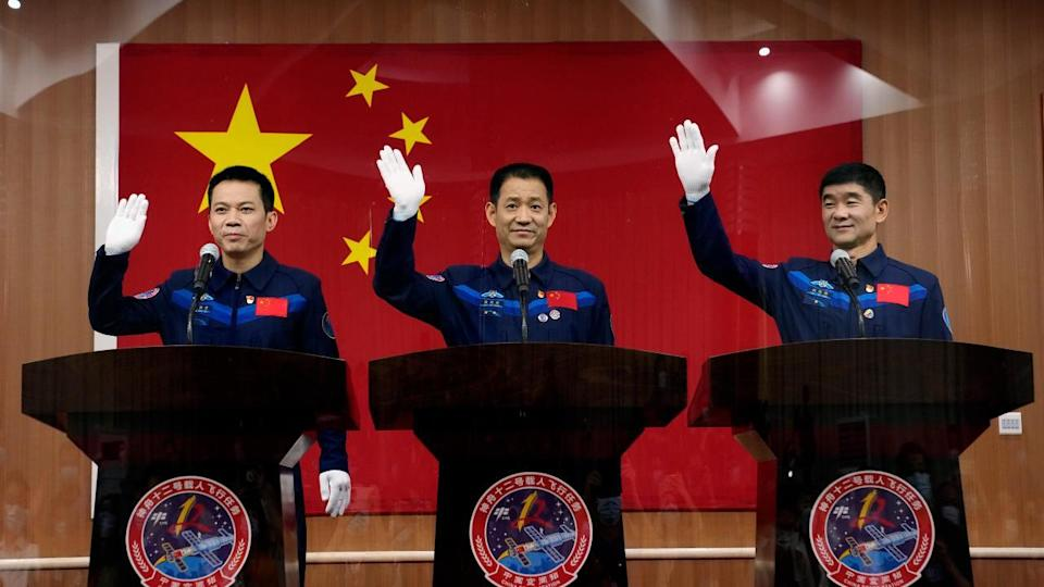 Chinese astronauts, from left, Tang Hongbo, Nie Haisheng, and Liu Boming wave during a press conference at the Jiuquan Satellite Launch Center ahead of the Shenzhou-12 launch from Jiuquan in northwestern China, Wednesday, 16 June  2021. Image credit: AP Photo/Ng Han Guan