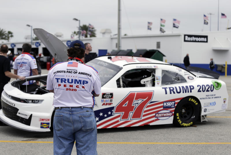 Crew members make adjustments to Joe Nemecheck's car sponsored by Patriots PAC of America during practice for the NASCAR Xfinity Series auto race at Daytona International Speedway, Friday, Feb. 14, 2020, in Daytona Beach, Fla. Trump is scheduled to be present for the Daytona 500 on Sunday and he will find this environment as welcoming as one of his campaign rallies. (AP Photo/Terry Renna)