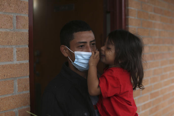 A migrant and his daughter wait for transportation to the airport, at Our Lady of Guadalupe Catholic Church in McAllen, Texas, on Palm Sunday, March 28, 2021. U.S. authorities are releasing migrant families at the border without notices to appear in immigration court, and sometimes without any paperwork at all. A spokesman for the National Border Patrol Council, a union that represents Border Patrol agents, said it was done to cut processing time at overwhelmed holding facilities. He said it takes an hour to 90 minutes to prepare one notice to appear in court. (AP Photo/Dario Lopez-Mills)