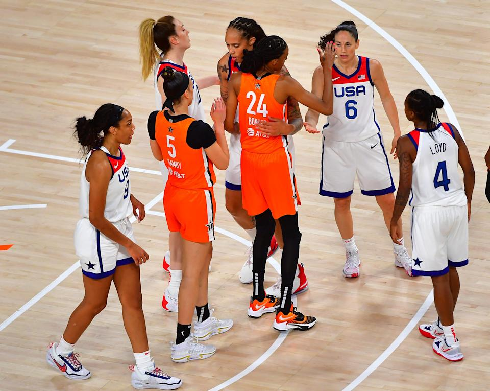 Players embrace on the court after the WNBA All-Star team defeated Team USA.