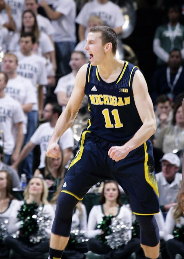 Michigan's Nik Stauskas celebrates his tie-breaking 3-pointer to put Michigan up late in the second half of an NCAA college basketball game against Michigan State, Saturday, Jan. 25, 2014, in East Lansing, Mich. Michigan won 80-75. (AP Photo/Al Goldis)