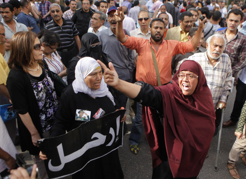 "Egyptian opposition activists shout anti-Muslim brotherhood slogans as anti-riot soldiers, not shown, prevent them from getting close to the Shura Council, the upper house of Parliament, during a protest against the new judicial law in Cairo, Egypt, Saturday, May 25, 2013. Arabic reads, "" depart."" (AP Photo/ Amr Nabil)"