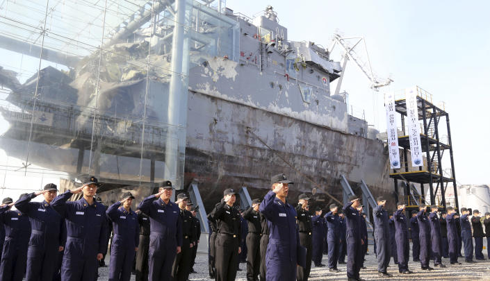 """South Korean navy sailors pay tribune to mark the third anniversary of the sinking of South Korean naval ship """"Cheonan"""" in front of the wreckage of the vessel at the Second Fleet Command of Navy in Pyeongtaek, south of Seoul, South Korea, Tuesday, March 26, 2013. An explosion ripped apart the 1,200-ton warship, killing 46 South Korean sailors near the maritime border with North Korea in 2010. (AP Photo/Yonhap, Shin Young-keun) KOREA OUT"""
