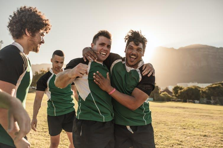 Young men celebrating after a rugby game