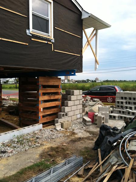 """This undated photo provided by Eileen Benner shows her Atlantic City home in the process of being elevated after it suffered severe flood damage during Oct. 2012 Superstorm Sandy, in New Jersey. Benner says elevating her home in Atlantic City, N.J., was """"a no-brainer"""" after it was damaged in the storm. """"I would tell anybody who has the money available to them to go ahead and do it."""" (AP Photo/Eileen Benner)"""