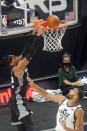 Sacramento Kings center Richaun Holmes, left, dunks as Utah Jazz center Rudy Gobert (27) looks on in the first half during an NBA basketball game Saturday, April 10, 2021, in Salt Lake City. (AP Photo/Rick Bowmer)