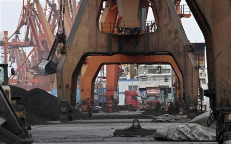 Stevedores walk under giant cranes as they wait to load coal imported from North Korea onto trucks at Dandong port in the Chinese border city of Dandong
