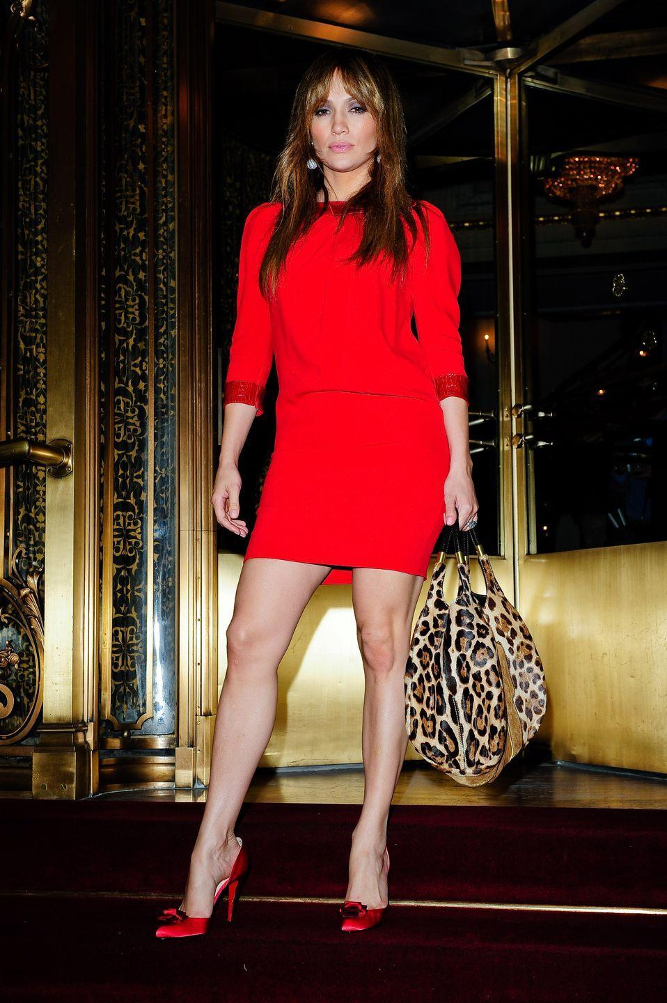 <p>J.Lo steps out of her NYC hotel in a long-sleeve red minidress, matching heels, and a leopard tote. </p>