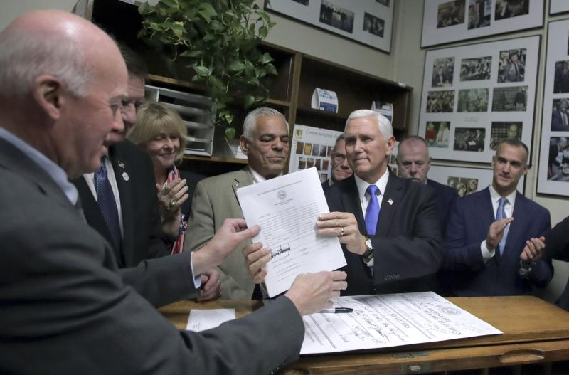 Republican Vice President Mike Pence files for President Donald Trump to be listed on the New Hampshire primary ballot to New Hampshire Secretary of State Bill Gardner, left, Thursday, Nov. 7, 2019, in Concord, N.H. (AP Photo/Charles Krupa)