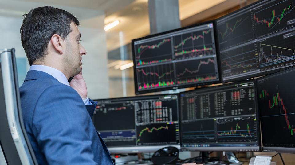 Male stock broker trading online watching charts and data analyses on multiple computer screens.