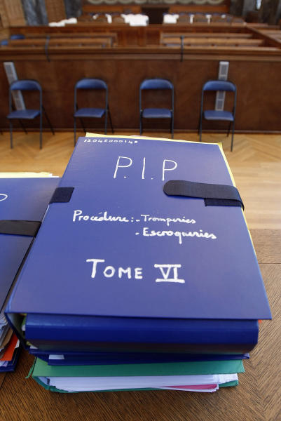 Documents concerning the Poly Implant Prothese (PIP) breast implant trial, are displayed in the courthouse in Marseille, southern France, Monday, Dec. 9, 2013. A court decides Tuesday whether Jean-Claude Mas, founder of the defunct PIP silicone breast implant company, is guilty of aggravated fraud by making tens of thousands of defective implants using industrial grade silicone, and selling them worldwide. The tribunal is expected to decide whether the German product-testing firm TUeV Rheinland was a victim of deception by Jean-Claude Mas or could be held responsible by failing to properly check the implants. More than 125,000 women received the implants until sales ended in March 2010. (AP Photo/Claude Paris)