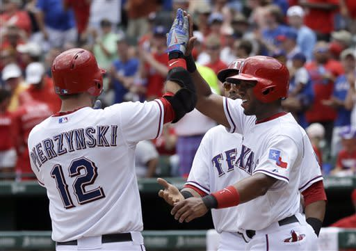 Texas Rangers' A.J. Pierzynski (12) is congratulated at the plate by teammates Elvis Andrus, right, and Nelson Cruz, rear, who were driven in on a three-run home run by Pierzynski off a pitch from Houston Astros' Erik Bedard in the first inning of a baseball game on Sunday, July 7, 2013, in Arlington, Texas. (AP Photo/Tony Gutierrez)