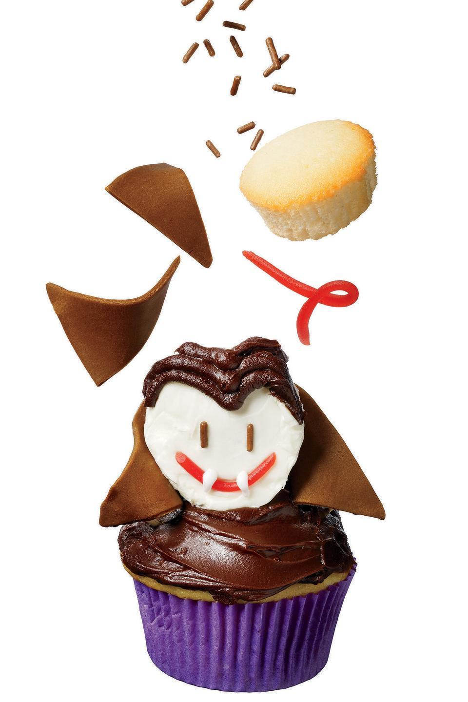 """<p>This recipe uses mini cupcakes for the Dracula face, licorice string for the mouth, and frosting for the rest of the features. </p><p><em><a href=""""https://www.womansday.com/food-recipes/food-drinks/recipes/a11432/fangtastic-dracula-cupcake-recipe-122728/"""" rel=""""nofollow noopener"""" target=""""_blank"""" data-ylk=""""slk:Get the Fang-tastic Dracula Cupcake recipe."""" class=""""link rapid-noclick-resp"""">Get the Fang-tastic Dracula Cupcake recipe.</a></em></p>"""