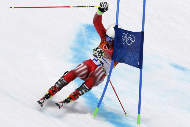 Switzerland's Gino Caviezel attempts to clears a gate during the first run of the men's alpine skiing giant slalom event at the 2014 Sochi Winter Olympics at the Rosa Khutor Alpine Center February 19, 2014. REUTERS/Stefano Rellandini (RUSSIA - Tags: SPORT SKIING OLYMPICS)