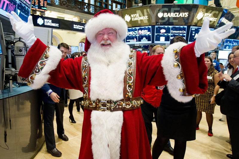 In this photo provided by the New York Stock Exchange, a man portraying Santa Claus visits the trading floor of the New York Stock Exchange, Wednesday Nov. 21, 2012 before he participated in opening bell ceremonies featuring the Macy's Thanksgiving Day Parade.  Stocks hovered near break-even Wednesday on Wall Street ahead of the Thanksgiving holiday. (AP Photo/NYSE Euronext, Ben Hider)