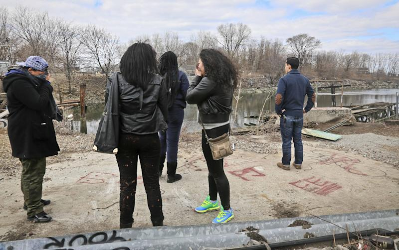 Friends mourn as they stand near Steinway Creek at an accident site on Saturday April 5, 2014 in New York. A driver of a car drove off a dead-end street in a desolate industrial area, flipped over a wooden curb into the East River inlet killing four passengers. The driver escaped serious injury and told officers at the scene in the Astoria section of Queens that the four were trapped in the submerged car. Fire department divers pulled the four victims from the car. Police identified them as 21-year-old Darius Fletcher, 19-year-old Jada Monique Butts, 19-year-old Crystal Gravely and 20-year-old Jaleel Furtado. They were pronounced dead at hospitals. (AP Photo/Bebeto Matthews)