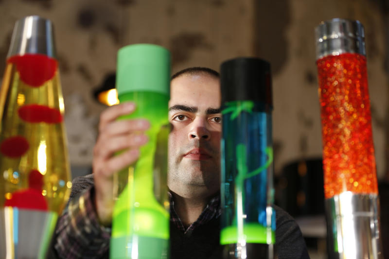 In this Monday, Aug. 19, 2013, Anthony Voss, lava lamp expert and collector, poses for the photographer in a shop in London with some of the lava lamps in his collection. The lava lamp, an iconic piece of British design and social trends, is celebrating its fiftieth birthday. Since its launch in 1963, Mathmos lava lamps have been in continuous production at their factory in Poole, Dorset. The company founder and eccentric inventor Edward Craven-Walker originally developed the lava lamp from an egg timer design he saw in a Dorset pub. (AP Photo/Lefteris Pitarakis)