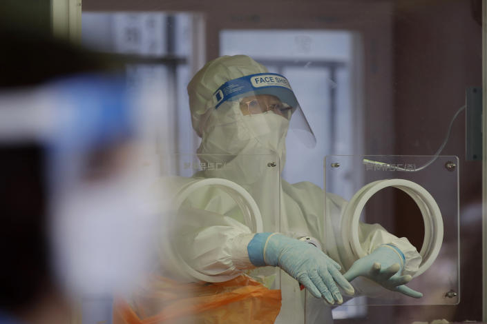 A medical worker wearing protective gear prepares to take a sample at a temporary screening clinic for coronavirus in Seoul, South Korea, Saturday, April 10, 2021. (AP Photo/Lee Jin-man)