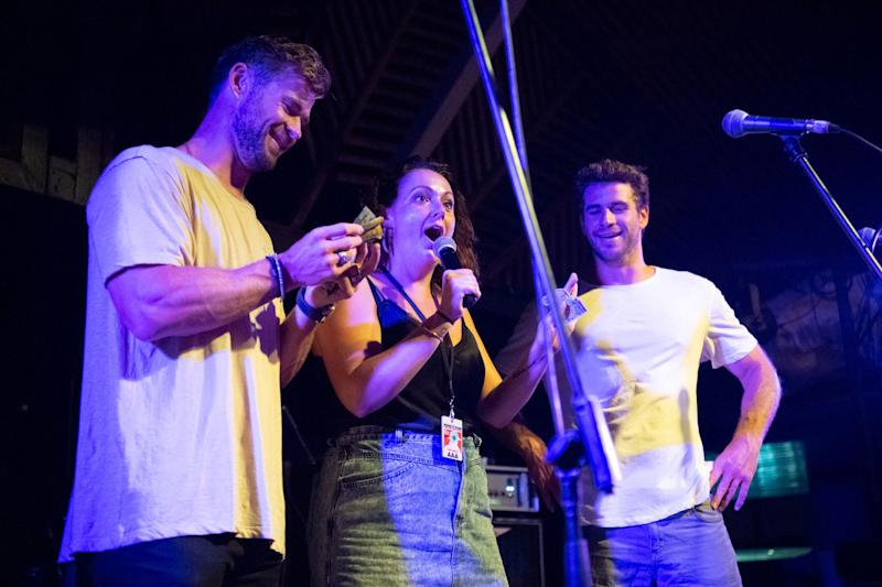 Celeste Barber looks happy on stage with Liam Hemsworth and Chris Hemsworth
