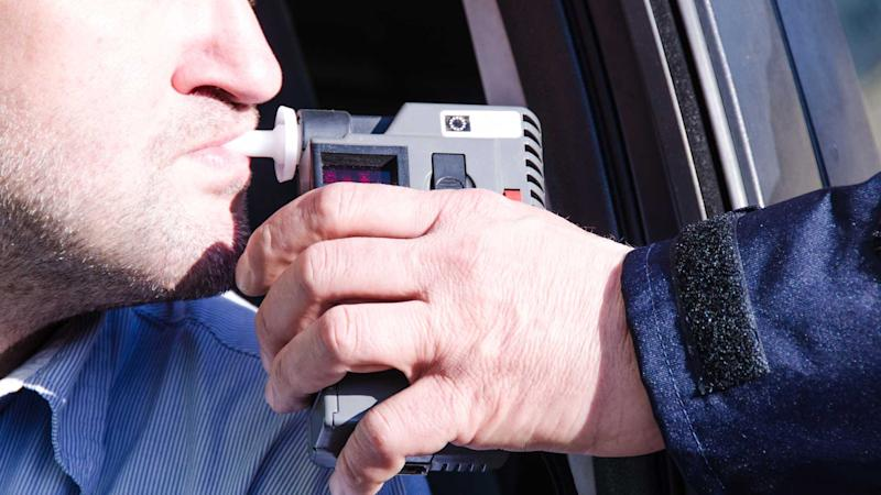 Driver is given breathalyser test by policeman