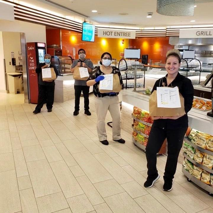 "<div class=""caption"">Food service workers handing out staff meals at UC San Diego Health</div><cite class=""credit"">Photo courtesy of Sadie Clements</cite>"
