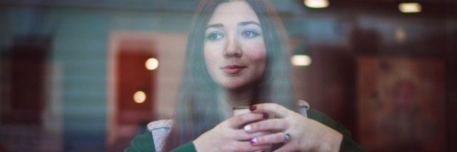 photo of dark haired young woman in coffee shop with coffee and croissant