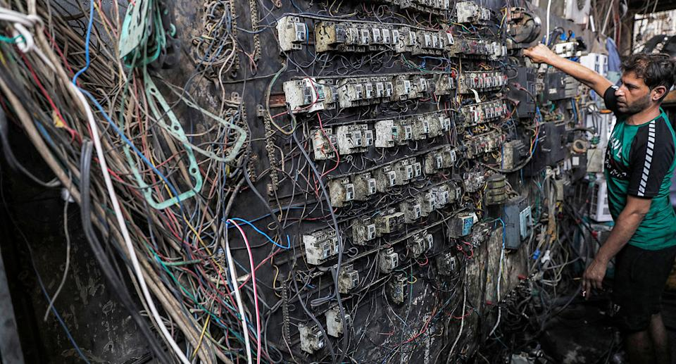A technician controls an electric switch board connecting homes to privately-owned electricity generators in a suburb of Iraq's capital Baghdad on June 30, 2021 as the national electric grid is experiencing outages amidst a severe heat wave. (Photo by AHMAD AL-RUBAYE / AFP) (Photo by AHMAD AL-RUBAYE/AFP via Getty Images)