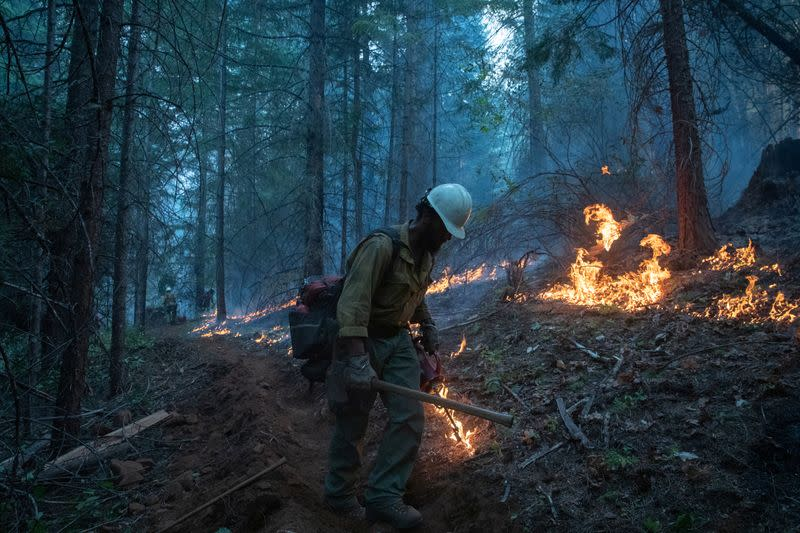 A firefighter from Las Vegas takes part in a firing operation near the Obenchain Fire in Butte Falls, Oregon