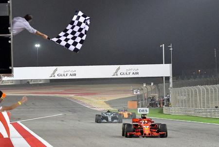 Formula 1 F1 - Bahrain Grand Prix - Bahrain International Circuit, Sakhir, Bahrain - April 8, 2018. Ferrari's German driver Sebastian Vettel crosses the finish line to win the Bahrain Formula One Grand Prix at the Sakhir circuit in Manama on April 8, 2018.  Giuseppe Cacace/Pool via REUTERS