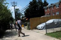 A man helps his relative move belongings out of their damaged house, near the scene of an explosion in a residential area of Baltimore