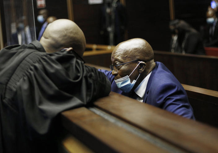 Former South African President Jacob Zuma, right, sits in the High Court, in Pietermaritburg, South Africa, Monday, May 17, 2021. Zuma and French arms company Thales face corruption, racketeering and money laundering charges linked to an arms deal. (Rogan Ward/Pool Photo via AP)