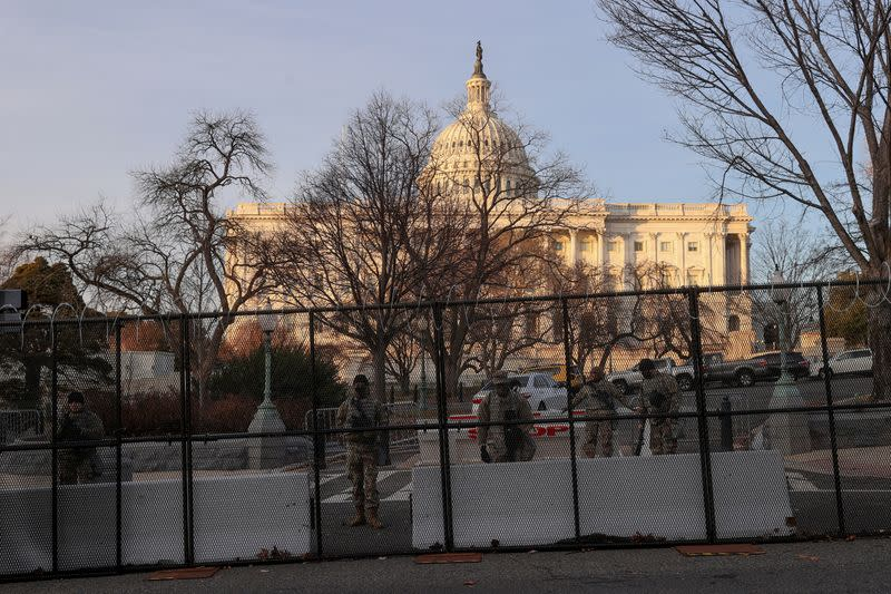 FILE PHOTO: Workers install razor wire atop the unscalable fence surrounding the U.S. Capitol in Washington