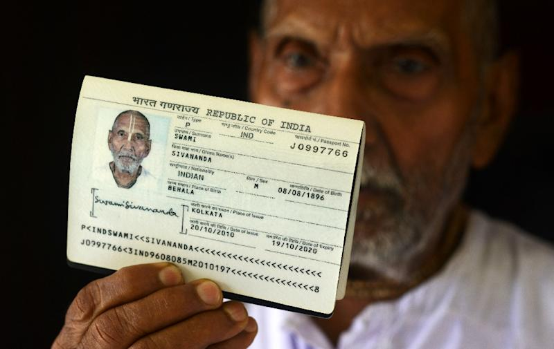 Indian monk Swami Sivananda holds up his passport showing his date of birth in the house of one of his followers in Kolkata (AFP Photo/Dibyangshu Sarkar)