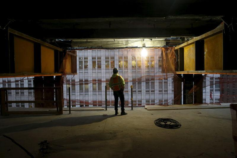 A worker is seen between two massive support beams inside 390 Madison Avenue, an office building in midtown Manhattan in New York that is undergoing a complete re-construction in New York