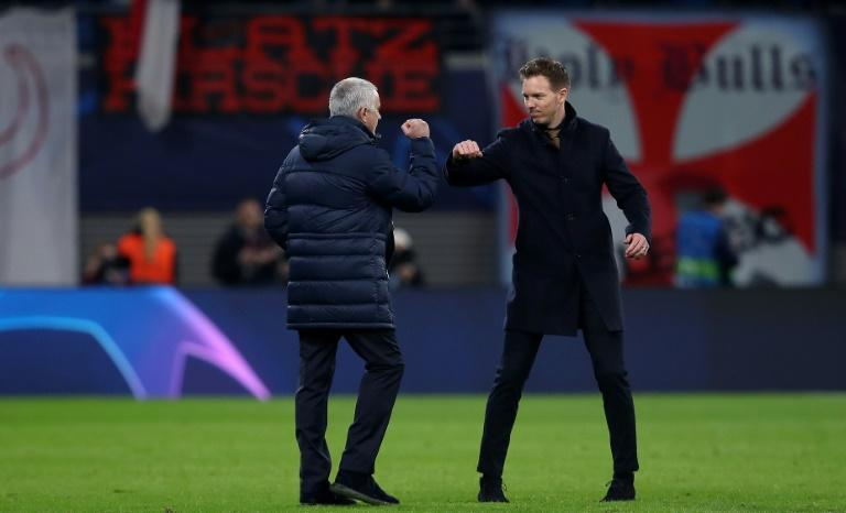 """Julian Nagelsmann (R) and Jose Mourinho """"elbow bump"""" after the UEFA Champions League match between RB Leipzig and Tottenham Hotspur, in Leipzig (AFP Photo/Ronny HARTMANN)"""