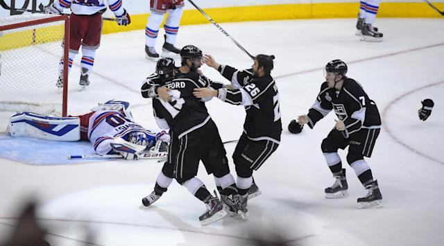 Members of the Los Angeles Kings, right, celebrate as they win in double overtime as New York Rangers goalie Henrik Lundqvist, center, of Sweden, reacts during the first overtime period in Game 5 of an NHL hockey Stanley Cup finals, Friday, June 13, 2014, in Los Angeles. (AP Photo/Mark J. Terrill)