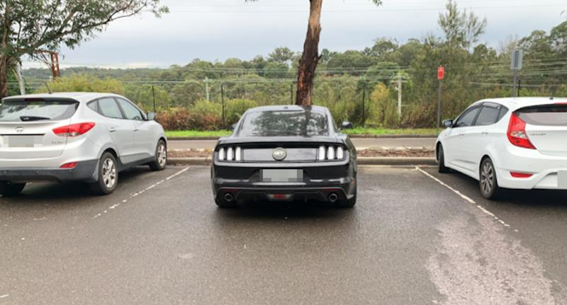 The black Ford Mustang parked in between two parking bays in Springwood.