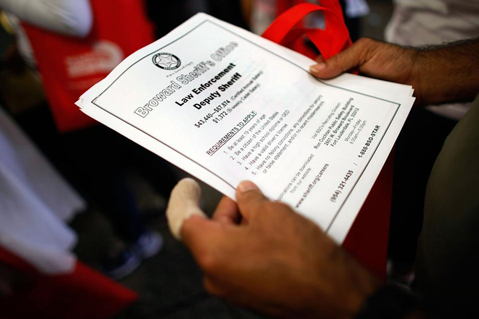 MIAMI - MAY 14:  A person looking for work holds a flyer for a job at the Broward Sheriffs office as they attend the Miami-Dade Community Action Agency job fair on May 14, 2009 in Miami, Florida. The Labor Department announced that the number of new jobless claims rose to 637,000, from a revised 605,000 the previous week.  (Photo by Joe Raedle/Getty Images)