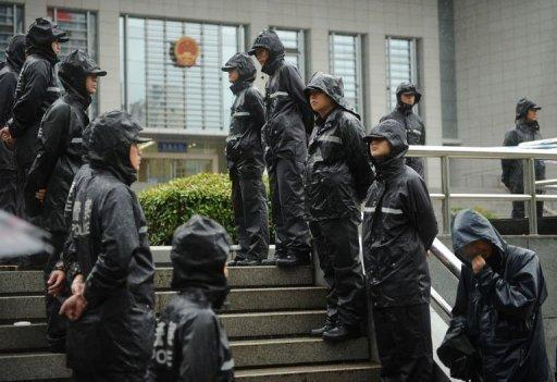Police stand guard outside the Intermediate People's Court in Hefei, Anhui province