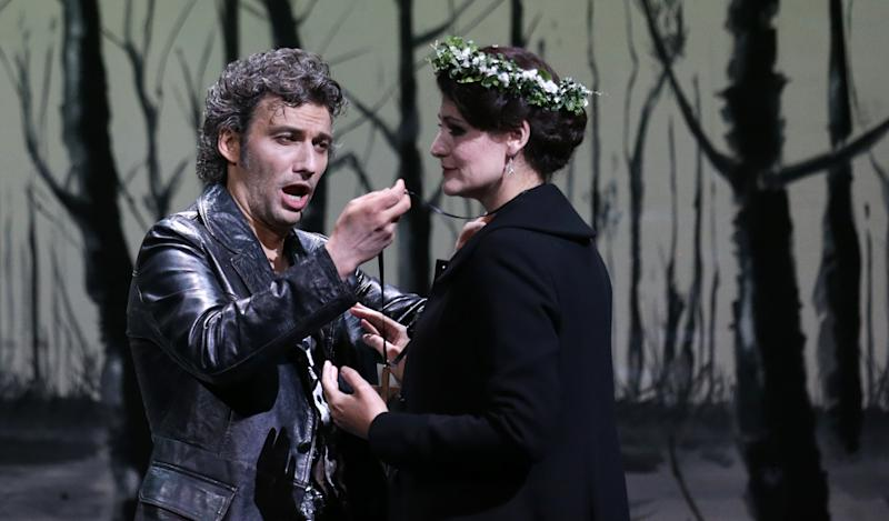 """In this picture taken Friday, June 21, 2013, Jonas Kaufmann, left, in the role of Manrico and Anja Harteros as Leonora sing during a dress rehearsal for the opera """"Il Trovatore"""" by Giuseppe Verdi in the Bavarian State Opera House in Munich, southern Germany. This wild new production by Olivier Py opened the company's annual Munich Opera Festival. It's a non-stop barrage of nightmarish images mixing styles and periods that assault the audience at lightning speed on a multi-tiered revolving set. (AP Photo/Matthias Schrader)"""