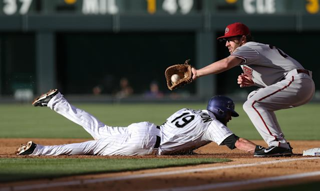 Arizona Diamondbacks first baseman Nick Evans, right, fields a pickoff throw as Colorado Rockies' Charlie Blackmon dives back into first base in the first inning of a baseball game in Denver on Tuesday, June 3, 2014. (AP Photo/David Zalubowski)