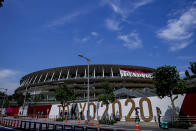 People wearing a protective masks pass by National Stadium, where the opening ceremony of the Tokyo 2020 Olympics will be held in less than two weeks is seen in the background Saturday, July 10, 2021, in Tokyo. (AP Photo/Kiichiro Sato)