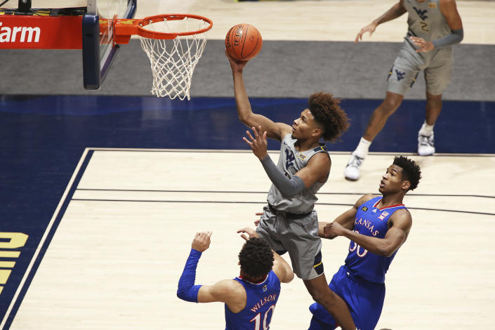 West Virginia guard Miles McBride (4) shoots while defended by Kansas forward Jalen Wilson (10) and guard Ochai Agbaji (30) during the first half of an NCAA college basketball game Saturday, Feb. 6, 2021, in Morgantown, W.Va. (AP Photo/Kathleen Batten)