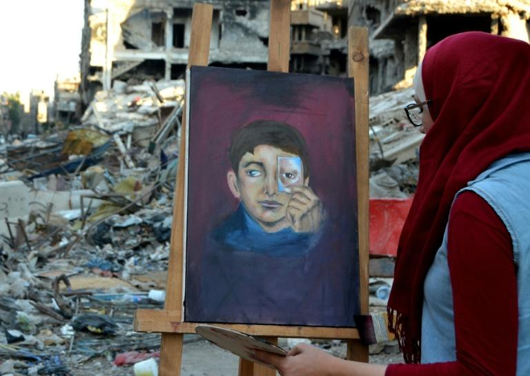 Artist Hinaya Kibabi works on a painting during a visit to the Yarmuk Palestinian refugee camp on the southern outskirts of Damascus on August 15, 2018