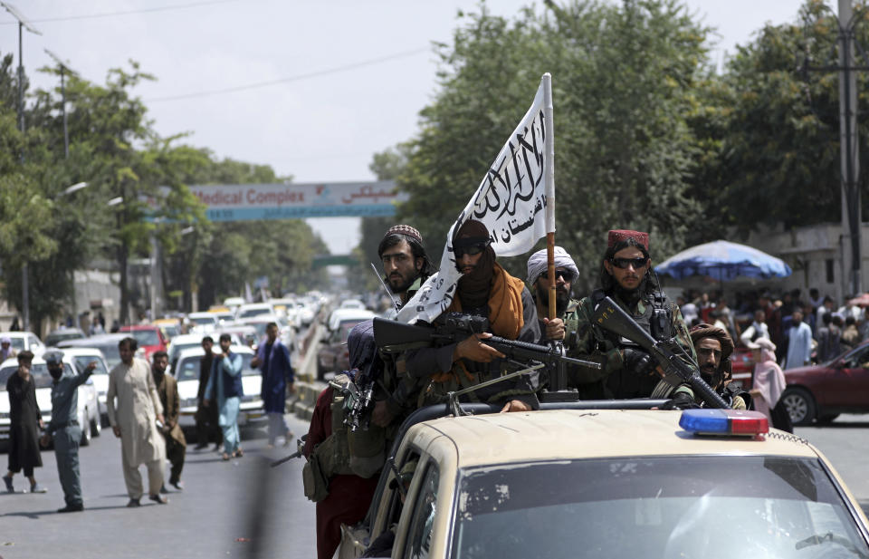 Taliban fighters display their flag while on patrol in Kabul, Afghanistan, Thursday, Aug. 19, 2021. The Taliban celebrated Afghanistan's Independence Day on Thursday by declaring they beat the United States, but challenges to their rule ranging from running a country severely short on cash and bureaucrats to potentially facing an armed opposition began to emerge. (AP Photo/Rahmat Gul)