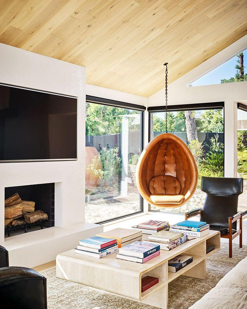 <p>The pared back design and floor-to-ceiling windows in this living room by Romanek Design Studio allow the eye to focus on the outdoor scenery beyond. But just because it's pared back does't mean it's boring—far from it, in fact. The modern, nature-inspired materials (hello, blond wood ceiling) create an understated canvas while the hanging leather chair and coffee table bring in some sculptural, playful flair. <br></p>